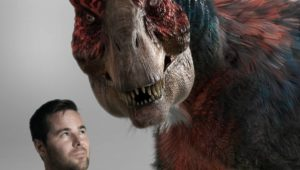 Photo of Matt Drummond posing with the VFX model of T. rex he rendered for his debut film, Dinosaur Island.